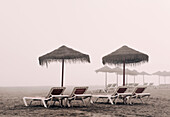 'Sunbeds And Umbrella On Playamar Beach In Off-Season On A Foggy Day; Torremolinos, Malaga, Costa Del Sol, Spain'