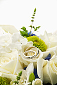 'A Bouquet Of White Roses With Two Wedding Bands Placed On Top; Portland, Oregon, United States Of America'