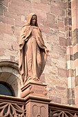 'Sandstone Statue Of Mary Looking Down On Top Of A Rail With Stone Work Of A Cathedral In The Background; Freiburg, Germany'