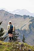 'Female Hiker On A Grassy Viewpoint Overlooking A Mountain Valley And Range; Oberstdorf, Germany'