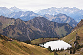 'High Angle View Of A Mountain Lake And Alpine Hut With Several Mountain Ranges In The Background; Oberstdorf, Germany'