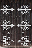 'Large Metal Decorative Hinges On A Weathered Wooden Barn Door; Fussen, Germany'