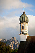 'Church Bell Tower With A Mountain Peak In The Background; Fussen, Germany'