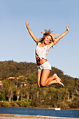 'A Young Woman Jumps In The Air; Currumbin, Gold Coast, Queensland, Australia'
