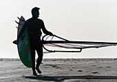 'A Man Walking On The Beach Carrying A Kite Surfboard; Tarifa, Cadiz, Andalusia, Spain'