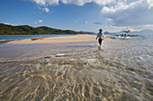 'A Male Tourist Walks Along The White Sand On A Small Island Near El Nido; Bacuit Archipelago, Palawan, Philippines'