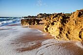 'A Rugged Rock Formation Along A Beach Near Chiclana De La Frontera; Andalusia, Spain'