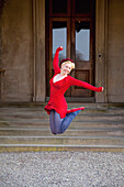 'A Young Woman Leaping Into The Air In Front Of Muckross House; Killarney, County Kerry, Ireland'