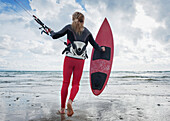 'A Young Woman With Her Equipment For Kite Surfing On Dos Mares Beach; Tarifa, Cadiz, Andalusia, Spain'