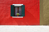 'A Flower Pot Sits In A Window With Shutters Open In Building Painted Bright Red; Burano, Venezia, Italy'