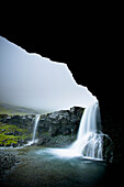 'Waterfalls Over A Rock Ledge As Viewed From Inside A Cave; Iceland'