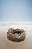 'A Boulder With A Hole In The Middle Filled With Water On A Beach; Moeraki, South Island, New Zealand'