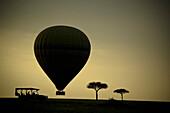 'Silhouette Of A Cart Hot Air Balloon And Trees At Sunset; Masai Mara, Kenya'