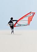 'A Windsurfer Walks On The Sand Of Punta Paloma Beach With His Board; Tarifa, Cadiz, Andalusia, Spain'