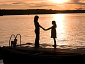 Silhouette Of Mother And Daughter On A Dock, Lake Of The Woods, Ontario, Canada