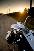 Motorcycle Parked On The Side Of The Road At Sunset