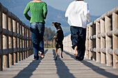 Two People Running With Dog