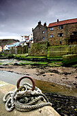 'Staithes, Yorkshire, England; Rope Tied To Pier By Beach'