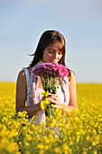 Woman Sniffing Purple Flowers While Standing In Golden Field