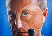 Threatening Looking Man With Magnifying Glass Held Up To Face