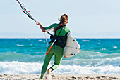 'A Woman With Her Kitesurfing Board Walking Into The Water; Tarifa, Cadiz, Andalusia, Spain'