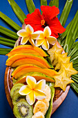 Studio Shot Pf A Variety Of Tropical Fruit Sliced On A Platter, With Flowers.
