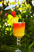 A Tequila Sunrise Garnished With Fruit In An Outdoor Setting.