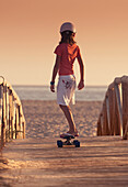 'A Young Person Skateboarding With Bare Feet Over A Wooden Boardwalk Towards The Beach; Tarifa, Cadiz, Andalusia, Spain'