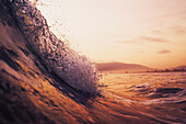 'A Large Wave In The Ocean At Sunset; Tarifa, Cadiz, Andalusia, Spain'
