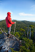 'A Man Wearing A Red Jacket Looks Out At The View Of Cox Bay Near Tofino; British Columbia, Canada'