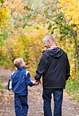 'Father And Son Walking On A Path In A Park In Autumn; Edmonton, Alberta, Canada'