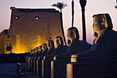 'Stone Statues And The Luxor Temple On The East Bank Of Luxor Along The Nile River; Luxor, Egypt'