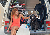 'A Woman Sits In The Back Of A Vehicle With A Surfboard And Petting A Dog; Tarifa, Cadiz, Andalusia, Spain'