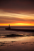 'A Lighthouse At Water's Edge At Sunset; Roker, Sunderland, Tyne And Wear, England'