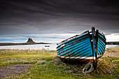 'A Weathered Boat Sitting On The Shore With Lindisfarne Castle In The Distance; Lindisfarne, Northumberland, England'