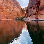 'Steep Rock Cliffs Along The Shoreline Reflected In The Colorado River; Arizona, United States of America'