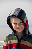 'Young Boy Smiling With A Hood On; Delta, British Columbia, Canada'