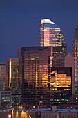 'Calgary Skyline At Dawn With City Lights And Deep Blue Sky With Buildings Reflecting The Orange Glow Of Sunrise; Calgary, Alberta, Canada'