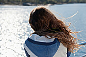 'A Girl's Hair Blowing In The Wind As She Stands At A Railing On The Water's Edge; Norway'
