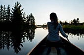 'A Girl Paddles A Boat On A Tranquil Lake At Sunset; Lake Of The Woods, Ontario, Canada'