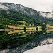 'Houses And A Forest On A Mountainside Reflected In Tranquil Water; Granvin, Norway'