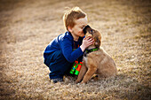 'A Boys Shows Affection To His Pet Dog; Spruce Grove, Alberta, Canada'
