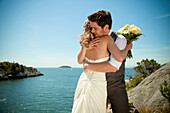 'A Bride And Groom Embrace At The Water's Edge In Whytecliff Park; Vancouver, British Columbia, Canada'