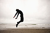 'An Individual Wearing A Wet Suit Jumping In Mid-Air On A Beach; French Beach, British Columbia, Canada'