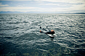 'A Surfer Lays On His Back On His Surfboard In The Water; Victoria, British Columbia, Canada'