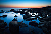 'Rocks In The Tranquil Water Along The Coast At Sunset; Tarifa, Cadiz, Andalusia, Spain'