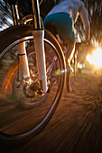 'The Motion Of A Bicycle Wheel As A Cyclist Rides On A Path At Sunset; Tarifa, Cadiz, Andalusia, Spain'