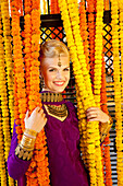 'A Woman Dressed In A Purple Sari Holding Onto The Hanging Strung Flowers; Ludhiana, Punjab, India'