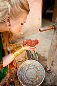 'A Woman With Mehndi On Her Palms Cups Her Hands To Collect Water From A Tap; Ludhiana, Punjab, India'