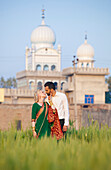 'A Mixed Race Couple Her Wearing A Sari Face To Face In A Field With A Temple In The Background; Ludhiana, Punjab, India'